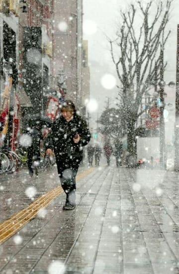 時折、激しく降る雪に肩をすぼめて歩く人たち=26日午後3時ごろ、大分市府内町