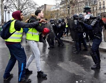 26日、パリのバスティーユ広場で警官隊と小競り合いをするデモ参加者(ゲッティ=共同)