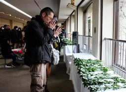ジョニーが飼育されていた屋外放飼場に向けて、手を合わせる来場者ら=神戸市立王子動物園