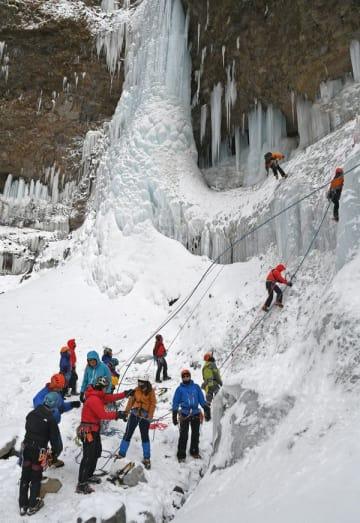 巨大な氷の壁となった滝を登る訓練の参加者たち=26日午前10時、日光市日光