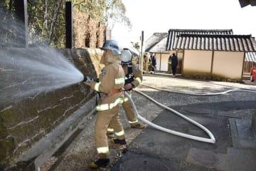 訓練で黒水家住宅への延焼を食い止めるため竹林に放水する消防士たち