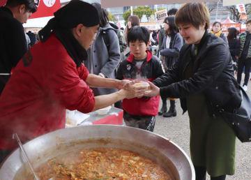 「ニッポン全国鍋グランプリ」で参加者(左)から鍋料理を受け取る来場者=27日午後、兵庫県姫路市