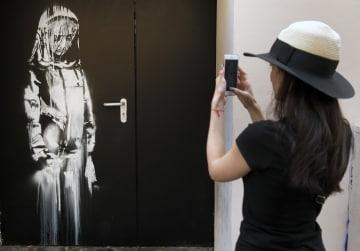 パリのバタクラン劇場でバンクシーの作品を撮る女性=2018年6月(ゲッティ=共同)