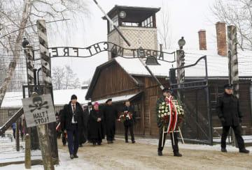 27日、アウシュビッツ強制収容所跡で、献花に向かう人々=ポーランド南部オシフィエンチム(ロイター=共同)