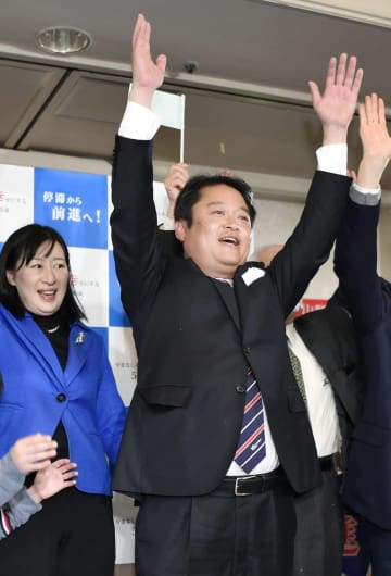 山梨県知事選で初当選を決め、万歳する長崎幸太郎氏=27日夜、山梨県昭和町