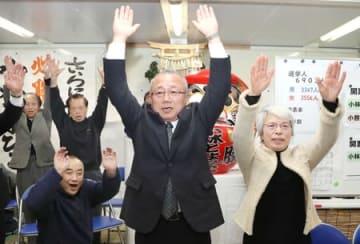 再選を決め、万歳する小林豊彦氏(中央)=27日午後8時前、弥彦村麓