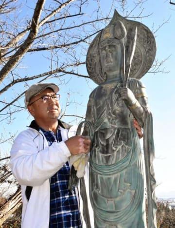 松谷希次さんの建てた観音像を清掃する勝希さん=延岡市・今山大師境内