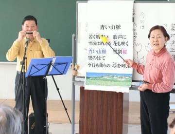 ボランティアでハーモニカの演奏会を行う築地光正さん(左)、スヱコさん夫婦。光正さんの演奏に合わせ、スヱコさんが指示棒で歌詞カードをなぞる=宇佐市の宇佐公民館