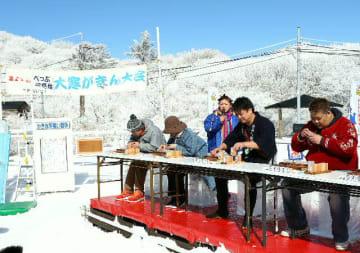 雪に覆われた会場で氷ずくめの競技に挑む参加者=27日、別府市の鶴見岳山上