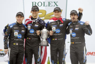 自動車の耐久レース、デイトナ24時間で優勝した小林可夢偉(左端)ら=デイトナビーチ(AP=共同)