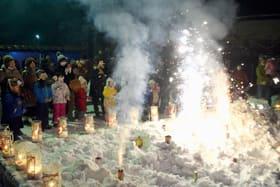 約300個のろうそくがゆらめく会場を一層彩る花火に見入る親子ら