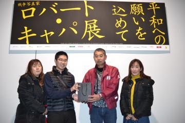 3000人目の入場者となり、記念品を贈られた若泉進さん(左から3人目)=土浦市大和町