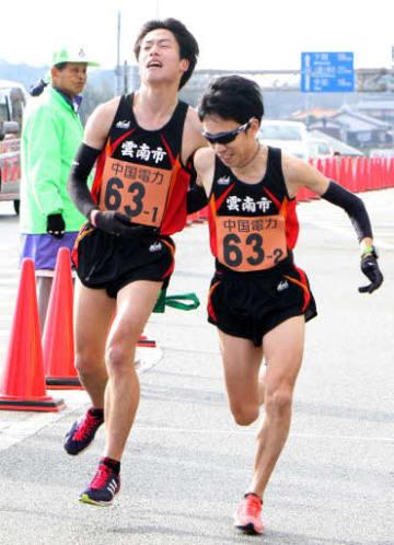 第1中継所で1区久我選手(左)からたすきを受け取り走りだす田中選手