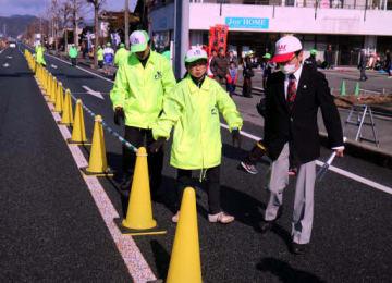 車道にコーンを置いてコースを確保するボランティアスタッフ