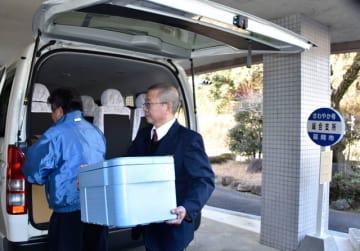 コミュニティバスから上鹿川地区の農産物を降ろす運転手
