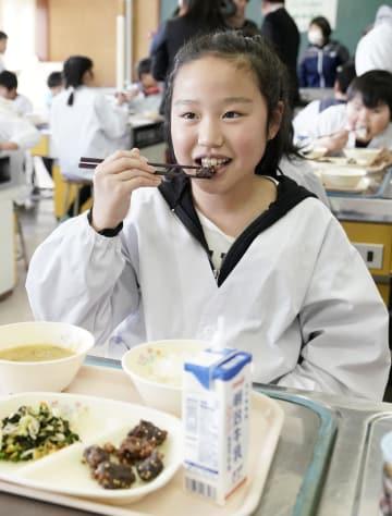 給食でクジラの竜田揚げを食べる子ども=28日午後、宮城県女川町