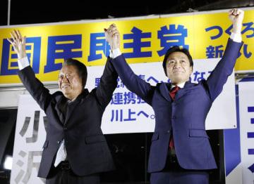 街頭演説を行い、両手を上げて聴衆にアピールする自由党の小沢共同代表(左)と国民民主党の玉木代表=28日夜、東京・有楽町