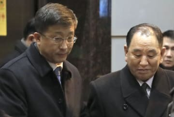 17日、北朝鮮の金英哲朝鮮労働党副委員長(右)に同行し、米国へ向け出発するキム・ヒョクチョル氏=北京国際空港(共同)