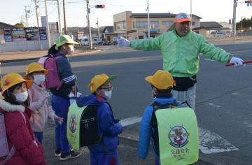通学児童の見守りを続ける石崎章さん(右奥)=18日午前7時45分ごろ、鉾田市串挽の県道「串挽交差点」
