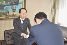 全国から室蘭市に寄せられた寄付金の目録を青山市長に手渡す山口局長(左)