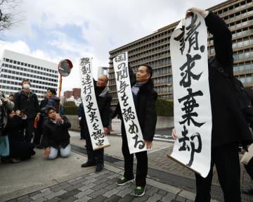 請求棄却の判決を受け、大阪地裁前で垂れ幕を掲げる原告ら=29日午前