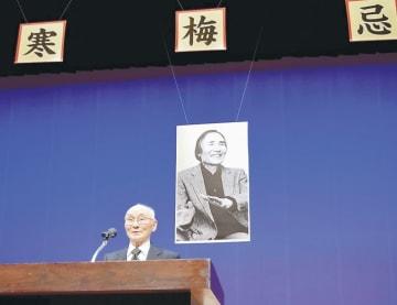 藤沢さんの写真を背にあいさつする萬年代表