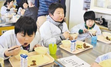 鯨肉の竜田揚げを頬張る児童