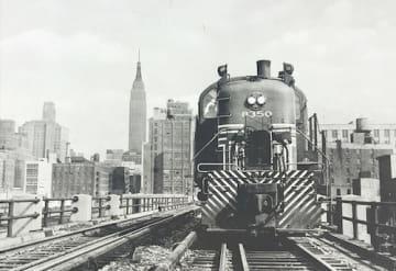 ハイラインで貨物を引く機関車。背後にエンパイアステートビルが見える(遊歩道脇のパネル展示から)
