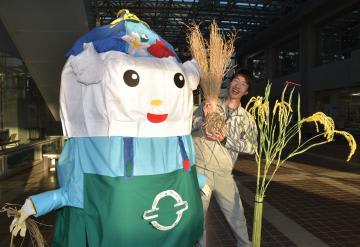 利根町観光協会のイメージキャラクター「とねりん」と製作した利根町職員(右)。電線や廃材で作った稲穂もある=利根町役場