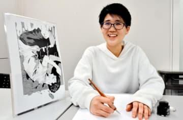 「ヘドロの子」の一場面(左)を傍らに、込めた思いや本格デビューへの意気込みを語る亀島潤斗さん=18日午後、広島市内