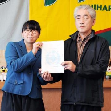 パートナーシップ宣誓証明書を笑顔で掲げる金田さん(左)ら=29日、千葉市役所