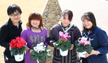 猫の遺灰を混ぜた土で育てた鉢植えのシクラメンを持つ障害者施設の通所者ら。花壇(背後)でも色鮮やかな花が育っている=大分市のおおいた動物愛護センター