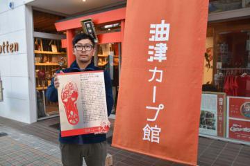 油津商店街に設置される元広島東洋カープ選手・新井貴浩さんの足形プレートを持つ杉本さん