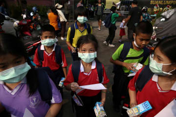 30日、タイの首都バンコクで、公立小中学校などの閉鎖を受け、マスク姿で迎えの車を待つ児童ら(ロイター=共同)