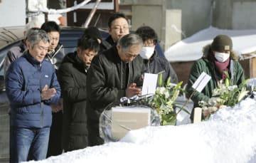 11人が死亡した共同住宅の火災現場で手を合わせる関係者ら=31日午前、札幌市東区