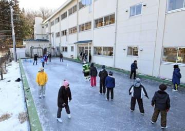 校舎裏に整備されたリンクでスケートを楽しむ子どもたち=30日午後、日光市鬼怒川小