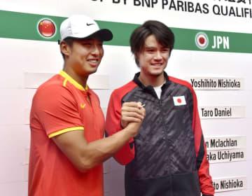 デビス杯の本戦進出決定戦で戦う中国選手(左)と握手する日本のダニエル太郎=31日、広州(共同)