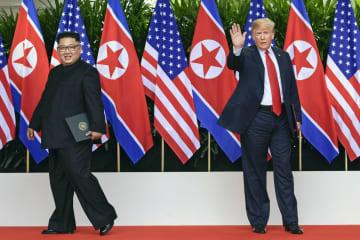 2018年6月、会談日程を終え、両国の国旗の前で別れる北朝鮮の金正恩朝鮮労働党委員長(左)とトランプ米大統領=シンガポール(AP=共同)