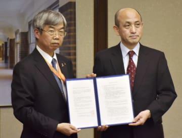 協定を締結した、名古屋市の海野稔博子ども青少年局長(左)と愛知県警の渡辺彰生活安全部長=31日午後、名古屋市