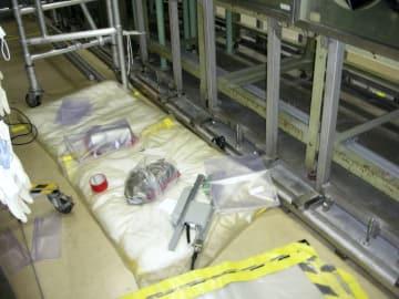 汚染が検出され、袋などで包まれた容器(左奥から三つ目、赤いテープの右)=30日、茨城県東海村の核燃料サイクル工学研究所(日本原子力研究開発機構提供)