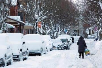 雪に覆われた道を歩く女性=1月31日、米ニューヨーク州(ロイター=共同)