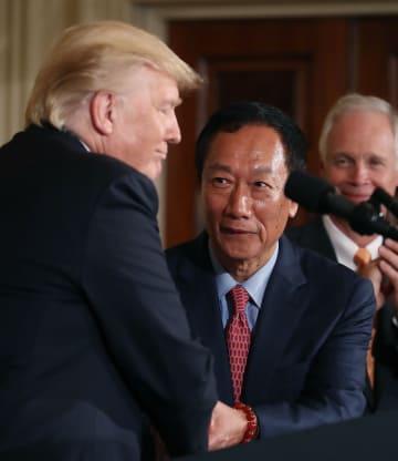 ホワイトハウスで握手するトランプ米大統領(左)と鴻海精密工業の郭台銘会長=2017年7月(ゲッティ=共同)