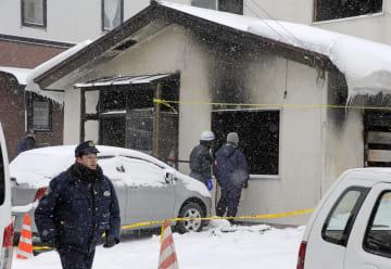 北海道小樽市の火災現場を検証する警察官ら=1日午後