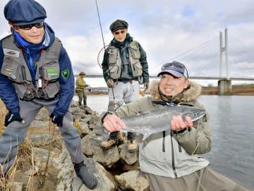 解禁初日に釣り上げたサクラマスを手に笑顔を見せる釣り人=2月1日、福井県福井市中角町