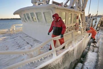 米マサチューセッツ州の港で、氷に覆われた釣り船を停泊しようとする人たち=1月31日(AP=共同)