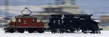 電気機関車(左)に押されて走行するラッセル車=1月20日、弘南線の平賀-館田間