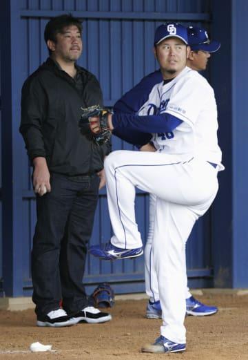 ブルペンで野茂英雄氏(左)が見守る中、投球練習をする中日・鈴木博=北谷