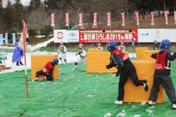 人工芝のコートで雪玉を投げ合うジュニアの部の選手たち