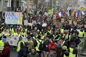 2日、パリで行進する黄色いベスト運動のデモ隊(共同)