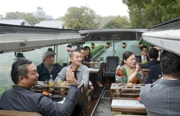 2階建てのレストランバスで、景色を眺めながら食事を楽しむ乗客ら。奥は熊本城=1月30日、熊本市